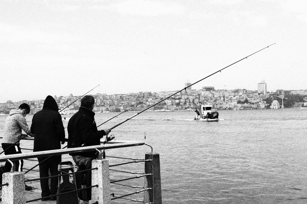 grayscale photo of people standing on boat
