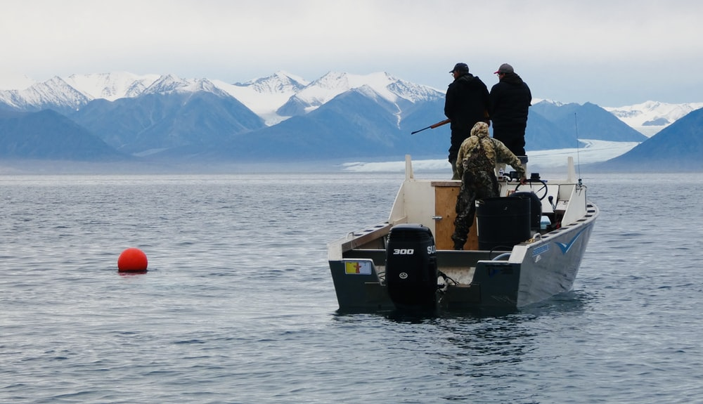 2 men in black jacket sitting on boat on lake during daytime
