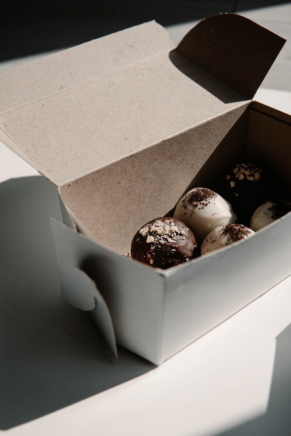 white and brown chocolate coated cookies in brown cardboard box