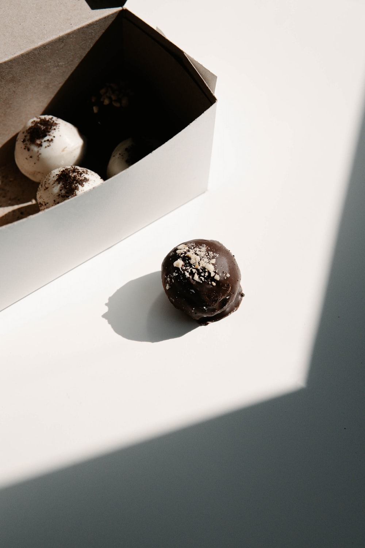chocolate coated doughnuts on white box