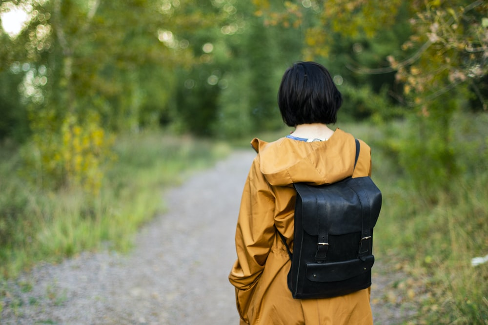 woman in black leather backpack walking on pathway during daytime