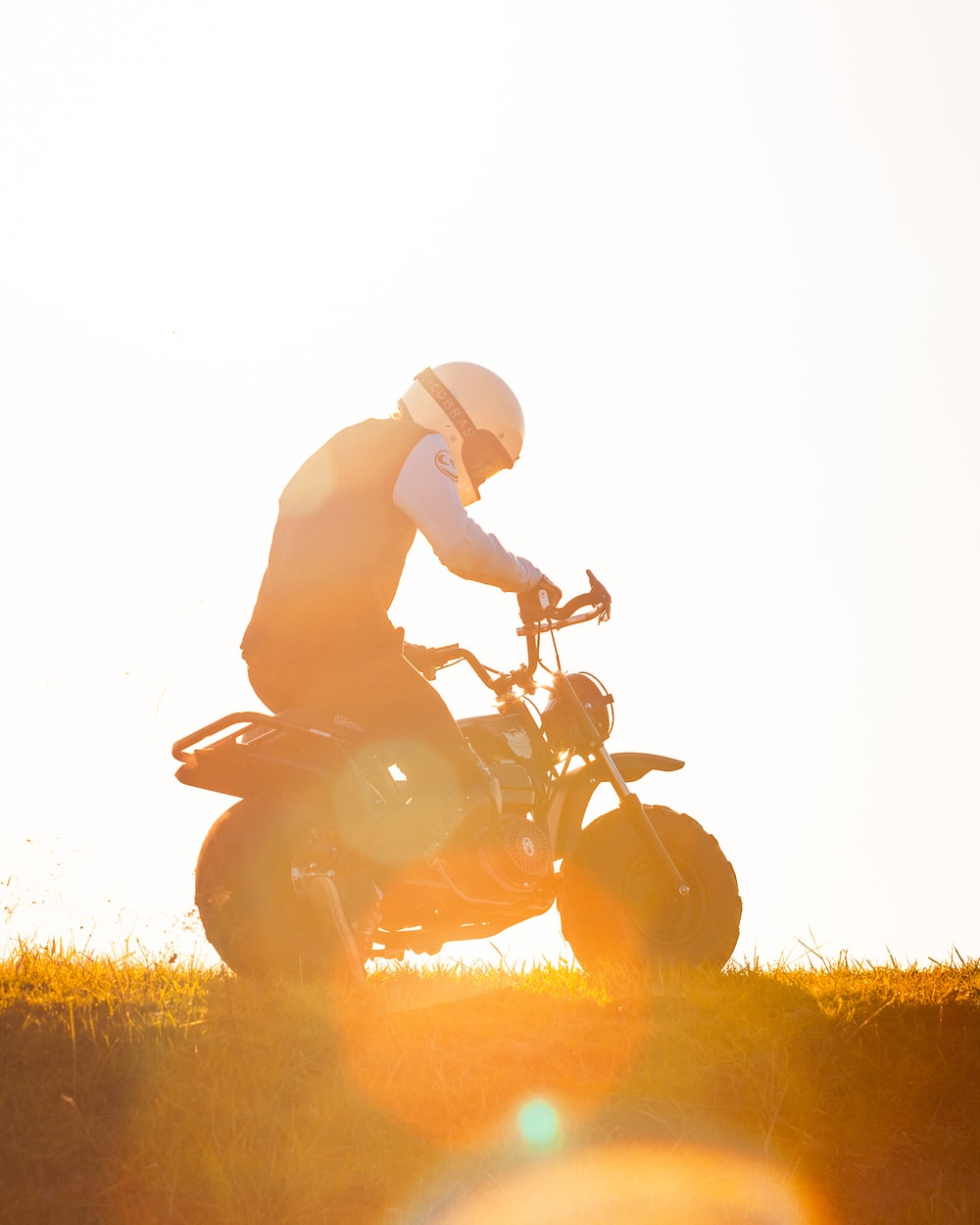 man riding motorcycle on grass field during daytime