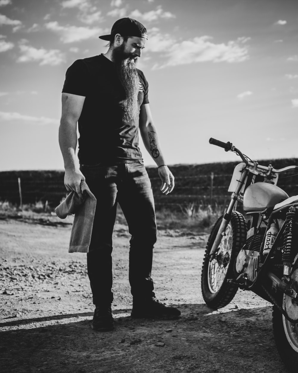 man in black t-shirt and pants standing beside motorcycle