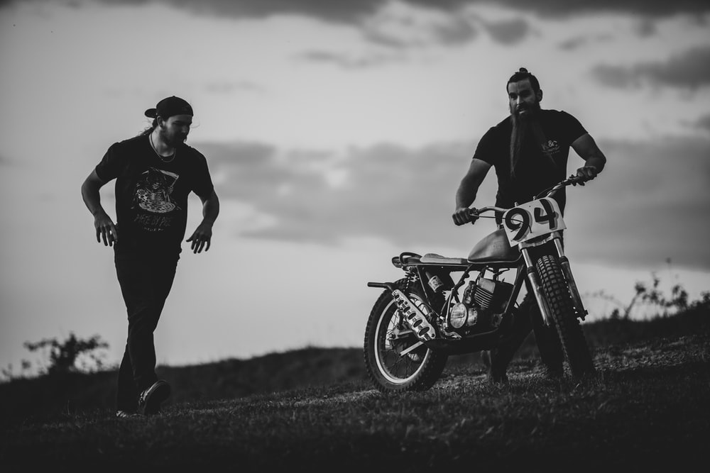 man and woman riding motorcycle in grayscale photography