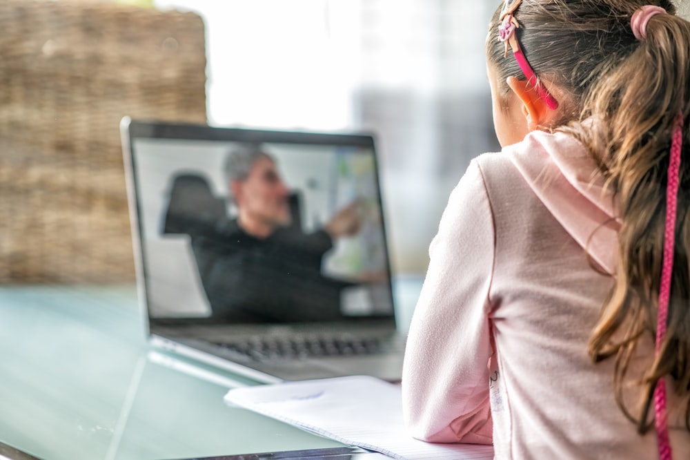 woman in pink long sleeve shirt sitting in front of macbook pro