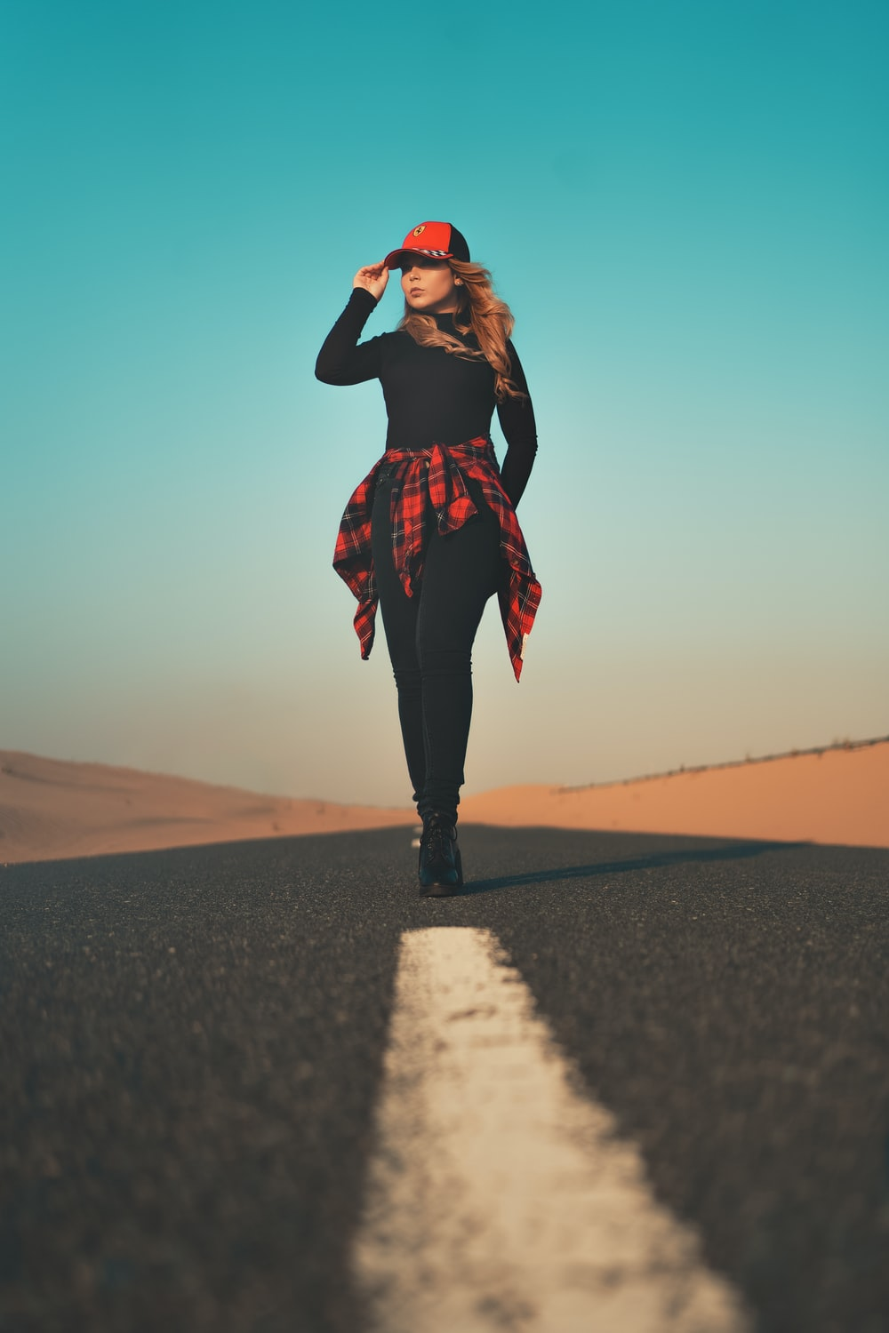 woman in black and red long sleeve shirt standing on brown sand during daytime