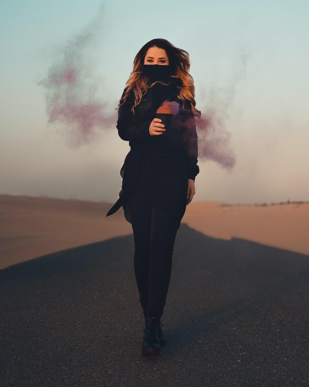 woman in black jacket standing on black asphalt road