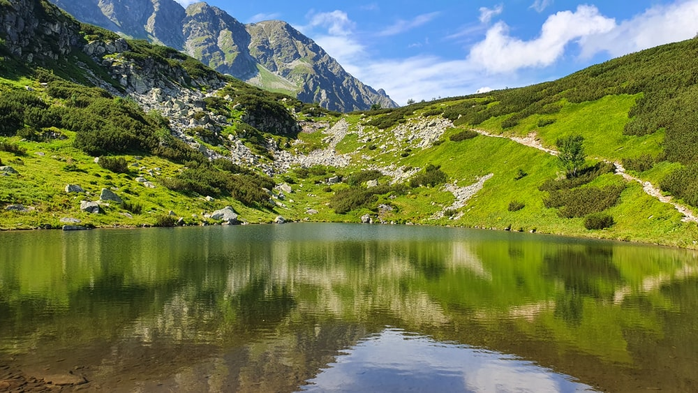 green and white mountains beside lake during daytime