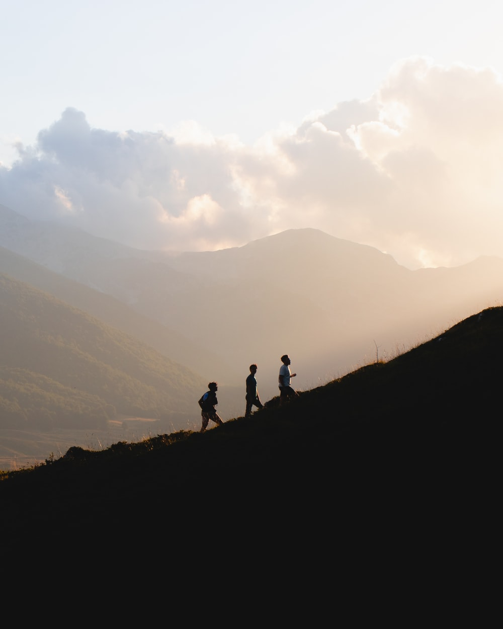 silhouette of 2 people standing on top of mountain during daytime