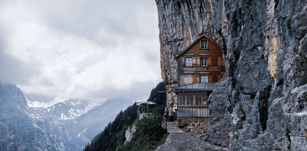 brown wooden house near mountain during daytime