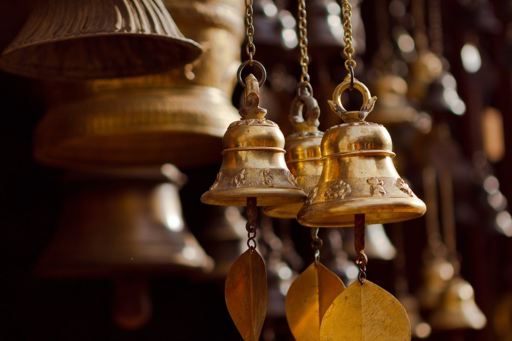 gold bell hanging on brown wooden wall
