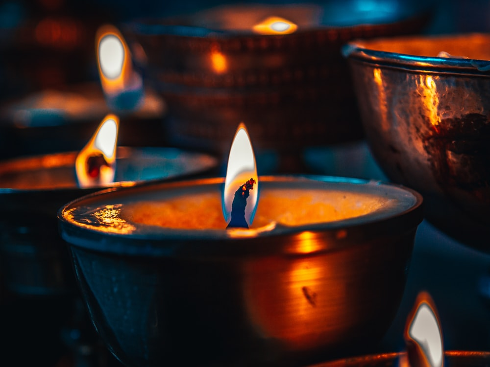 lighted candle in brown ceramic bowl