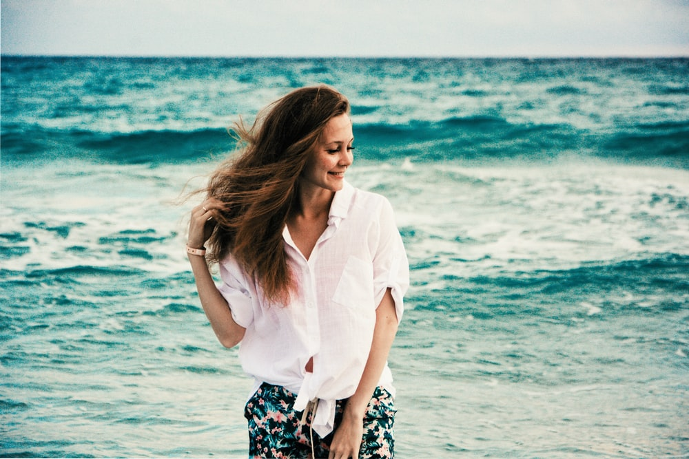 woman in white dress shirt standing on beach during daytime