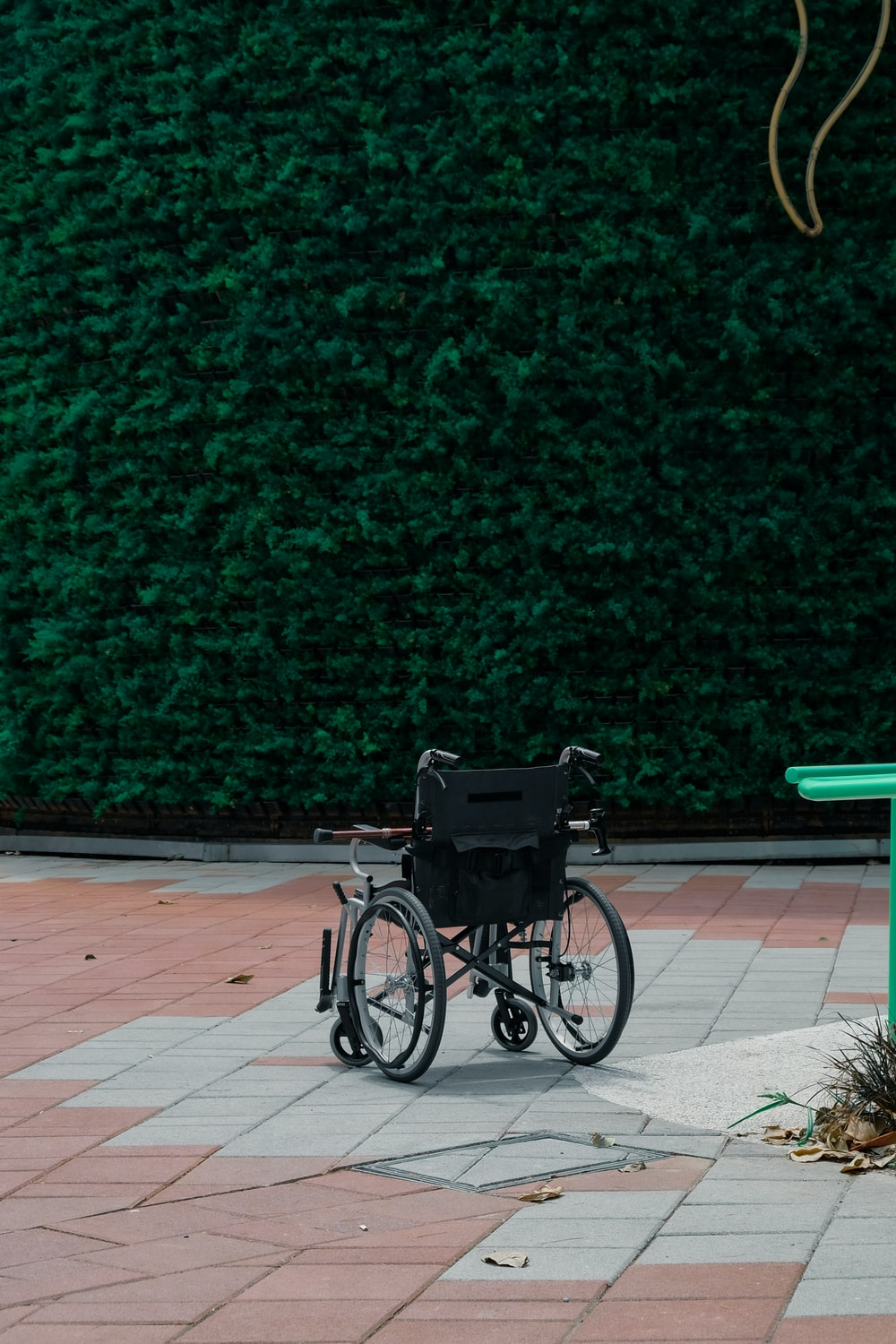 black bicycle parked beside green wall