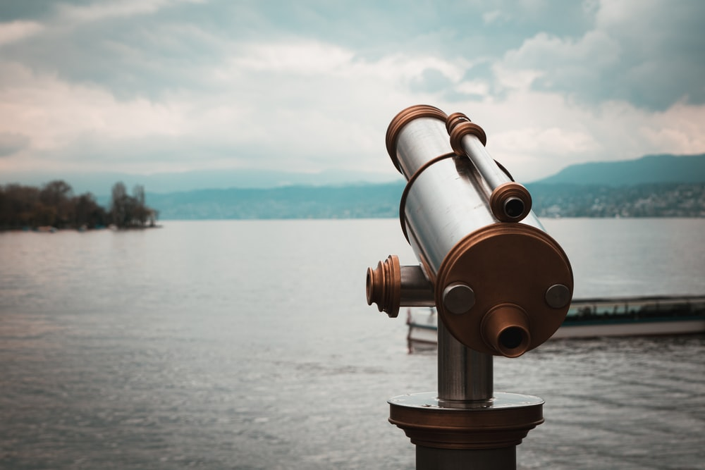 brown and silver telescope near body of water during daytime