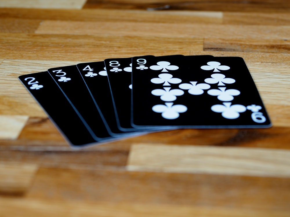 black and white playing card on brown wooden table