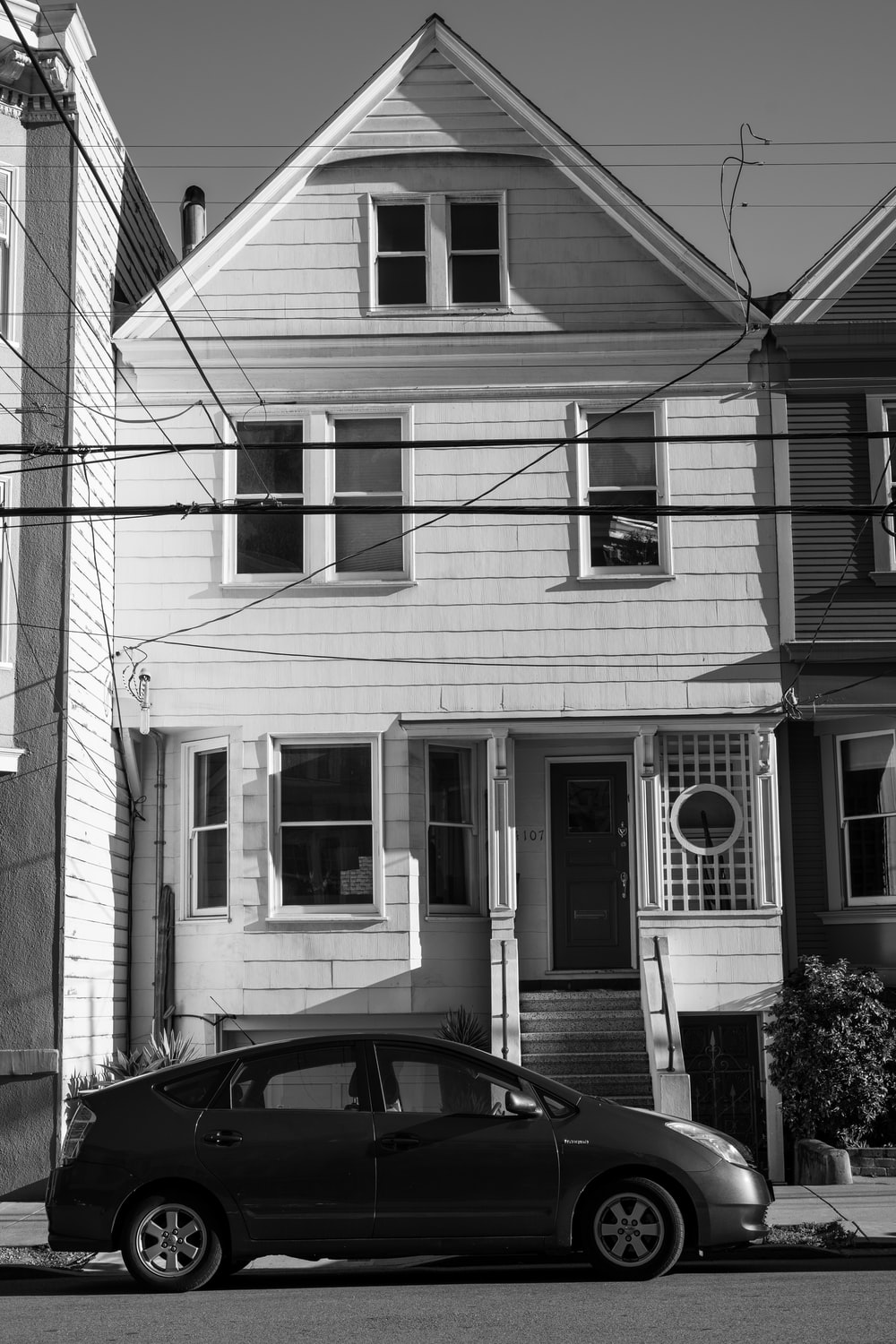 grayscale photo of car parked in front of house