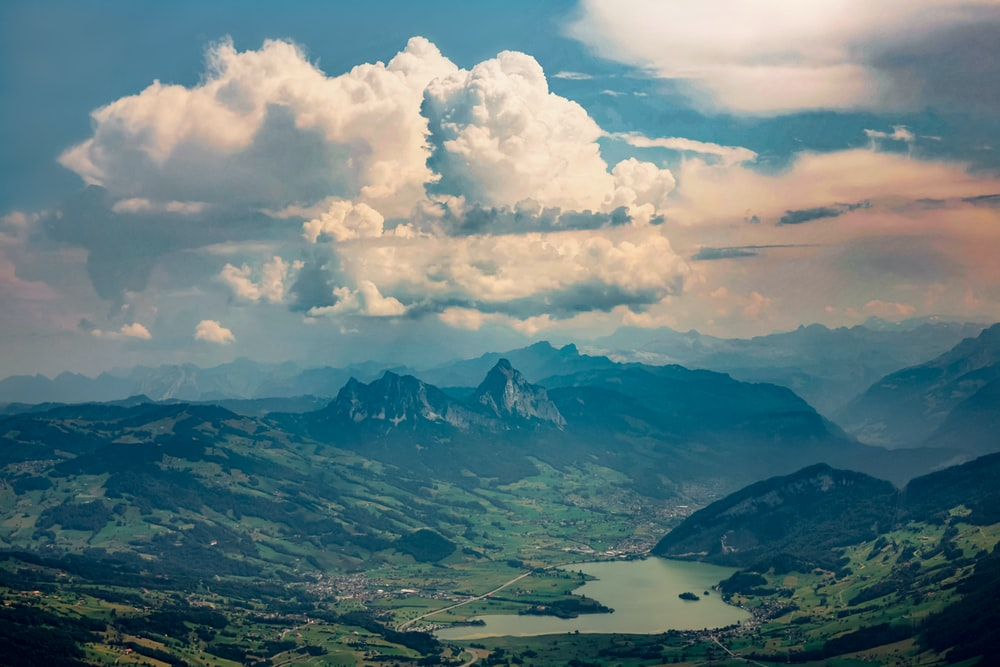 white clouds over mountains and lake