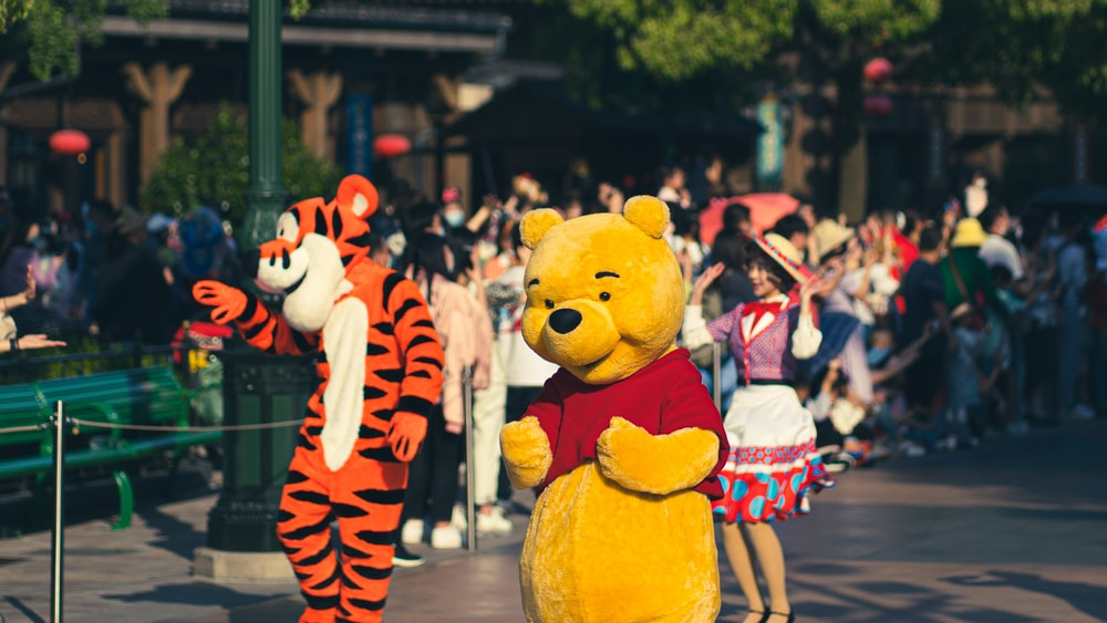 people standing near yellow bear statue during daytime