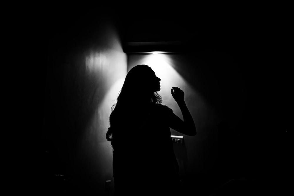 silhouette of woman in dark room