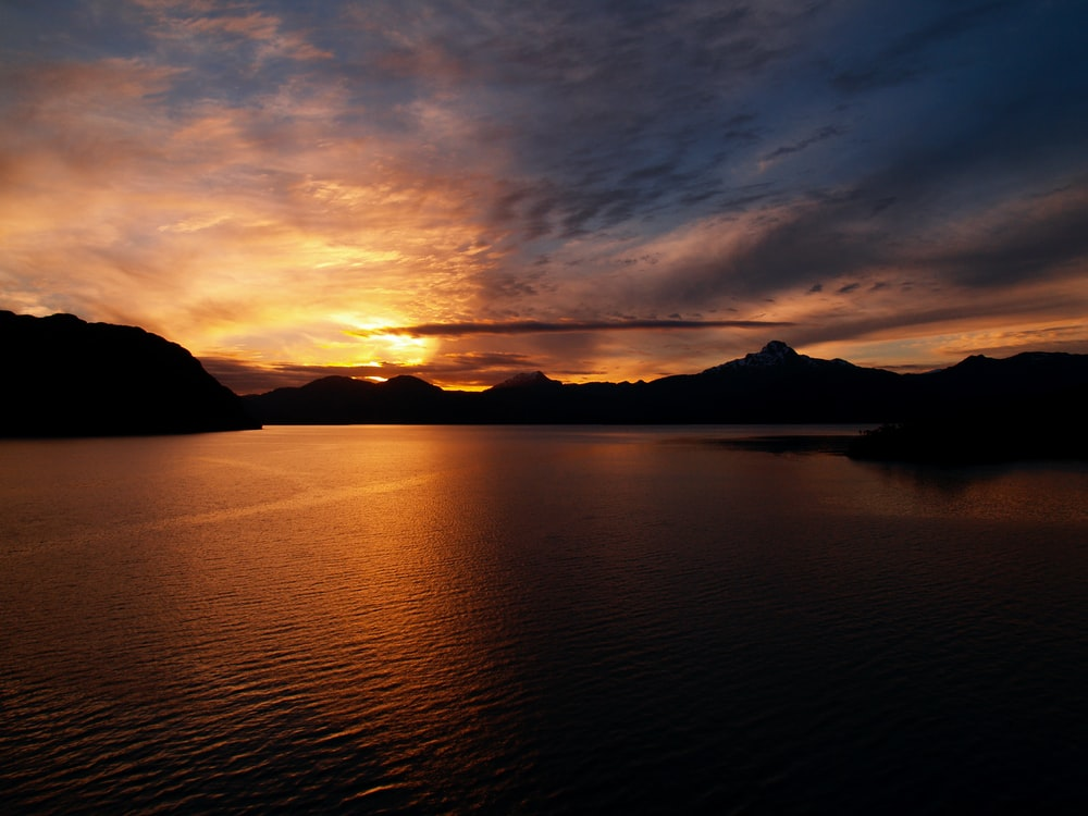 silhouette of mountain near body of water during sunset