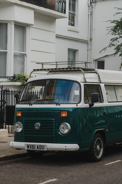 green and white volkswagen t-2 parked on sidewalk during daytime