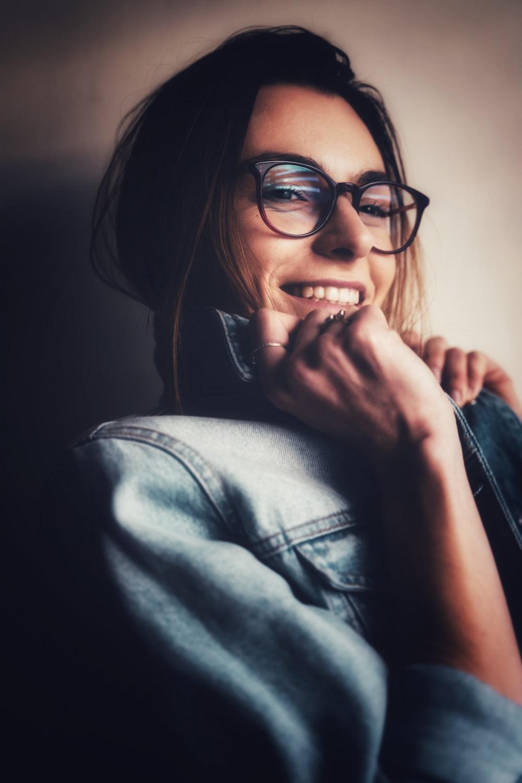 woman in black framed eyeglasses and blue denim jacket