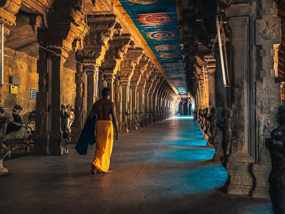 man in brown thobe walking on hallway