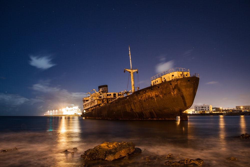 brown ship on sea during night time