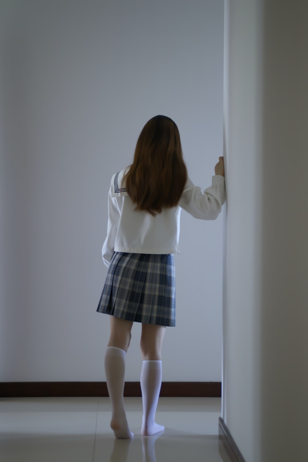 woman in white long sleeve shirt and black and gray plaid skirt