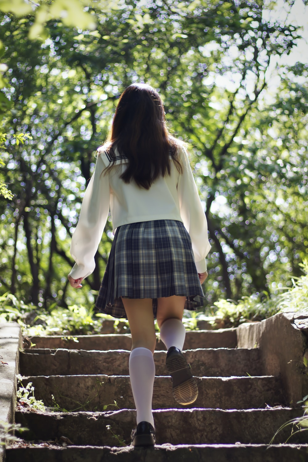 woman in white long sleeve shirt and blue and black plaid skirt standing on brown concrete