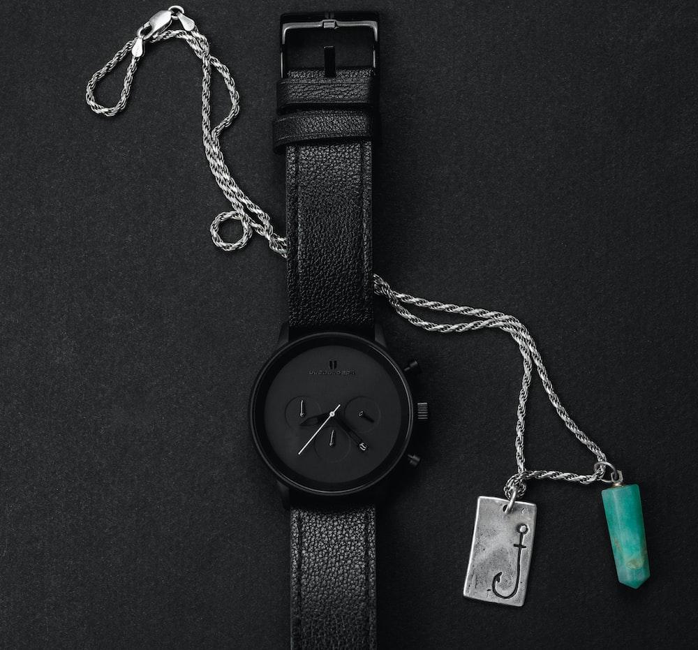 black round analog watch with black strap