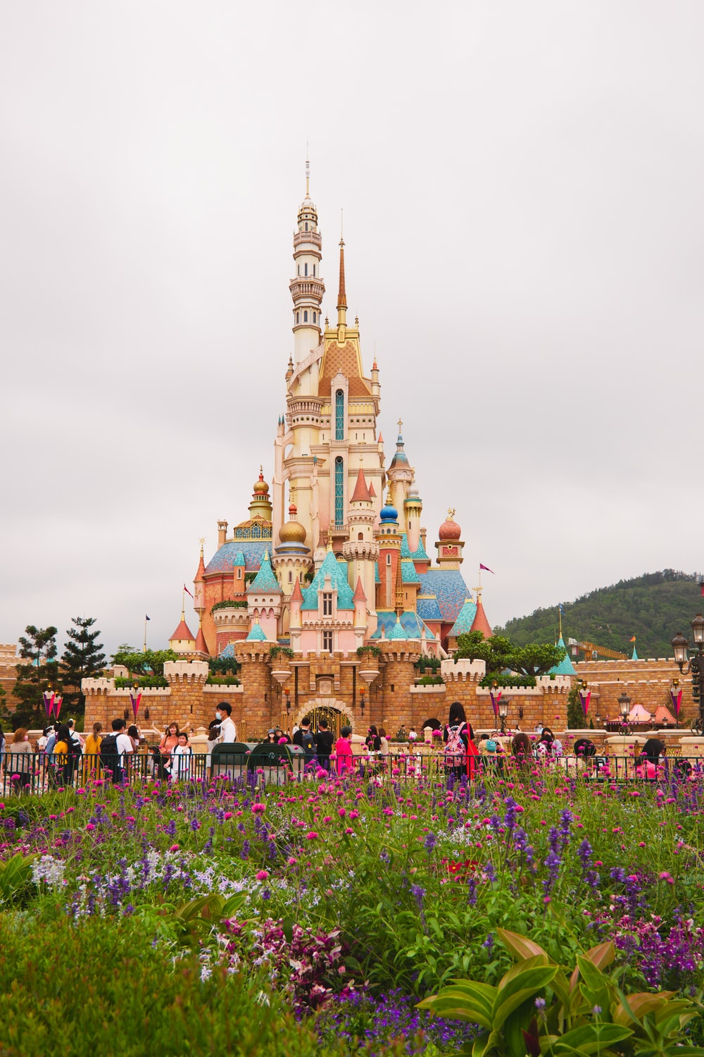 brown and green castle surrounded by green trees under white clouds during daytime