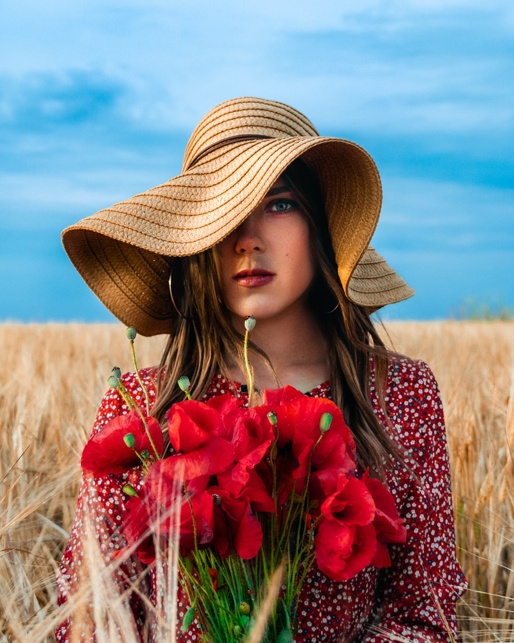woman in brown straw hat holding red flowers