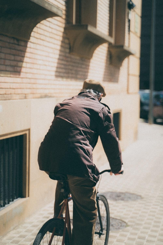 man in black jacket riding bicycle on street during daytime