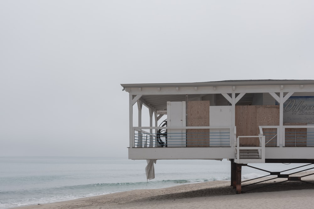 brown wooden lifeguard house on beach shore during daytime