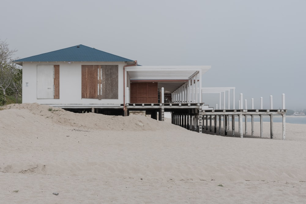 brown wooden house on white sand during daytime