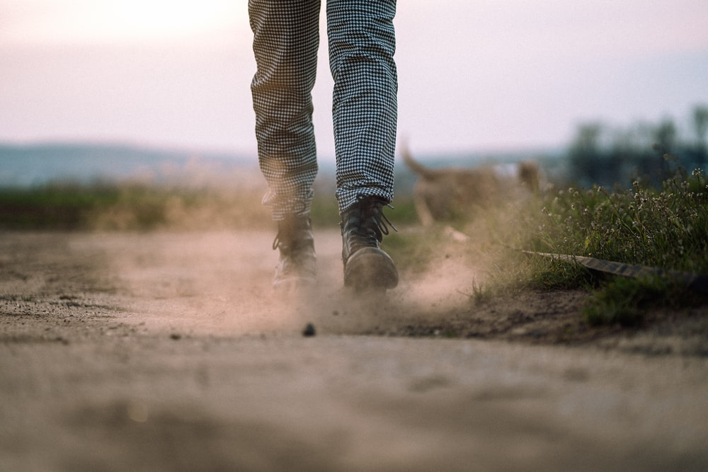 person in black and white striped pants walking on dirt road during daytime