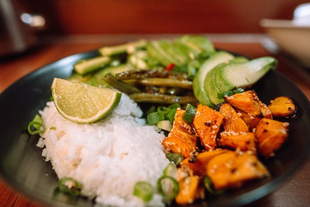 sliced carrots and green vegetable on white ceramic plate