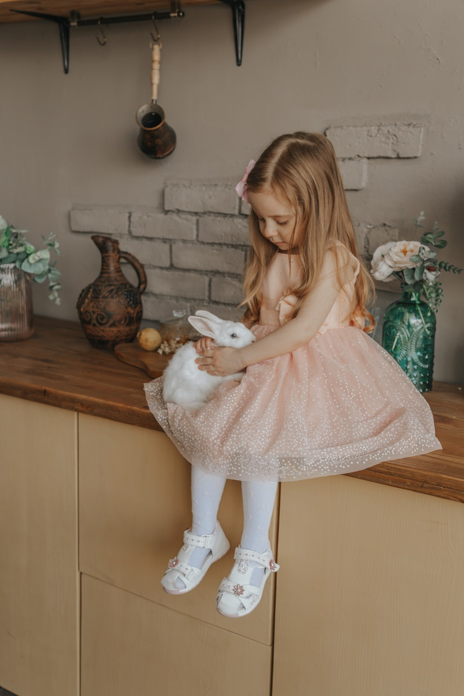 woman in pink dress holding white rabbit plush toy