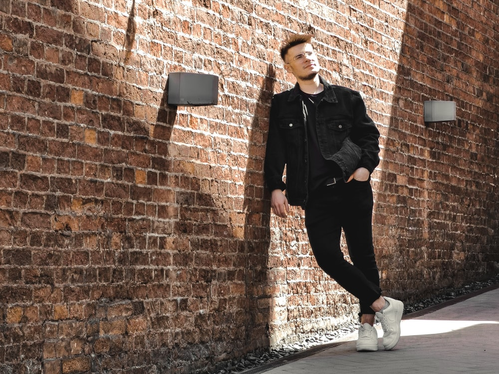 man in black leather jacket and black pants leaning on brown brick wall