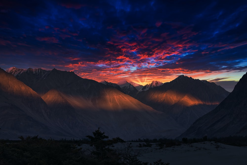 snow covered mountains during sunset