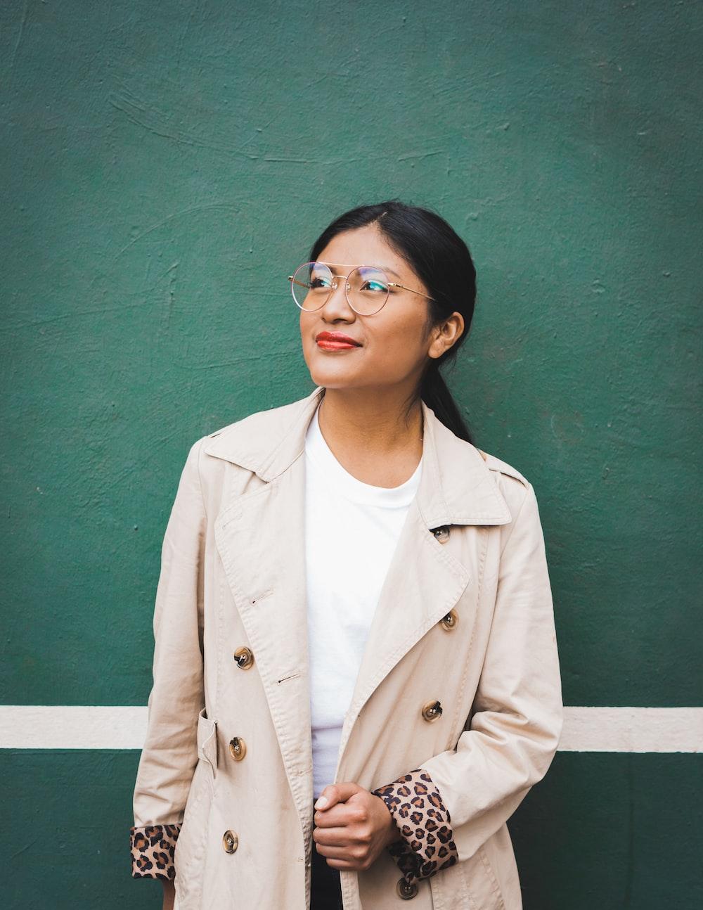 woman in beige coat standing near green wall