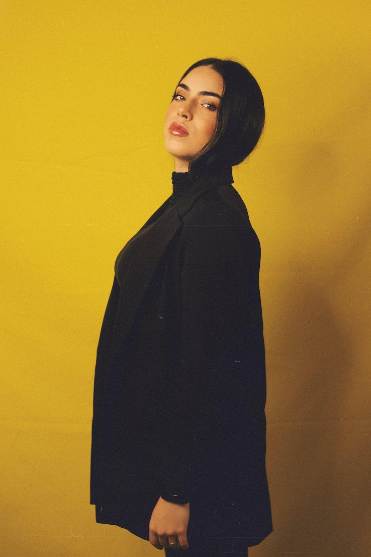 woman in black coat standing beside yellow wall