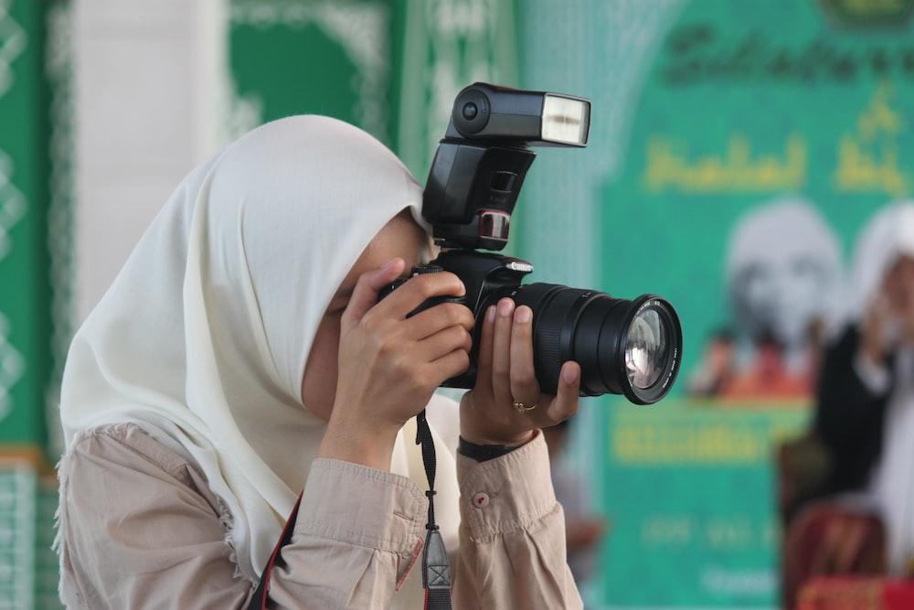 person in white hijab holding black dslr camera