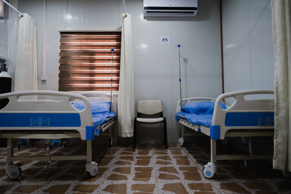 white split type air conditioner over white and blue hospital bed