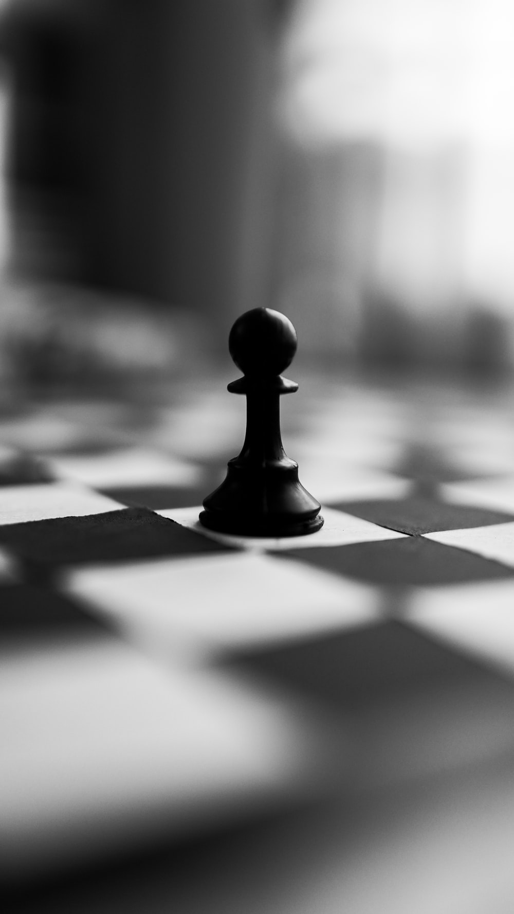 black chess piece on white and black checkered textile