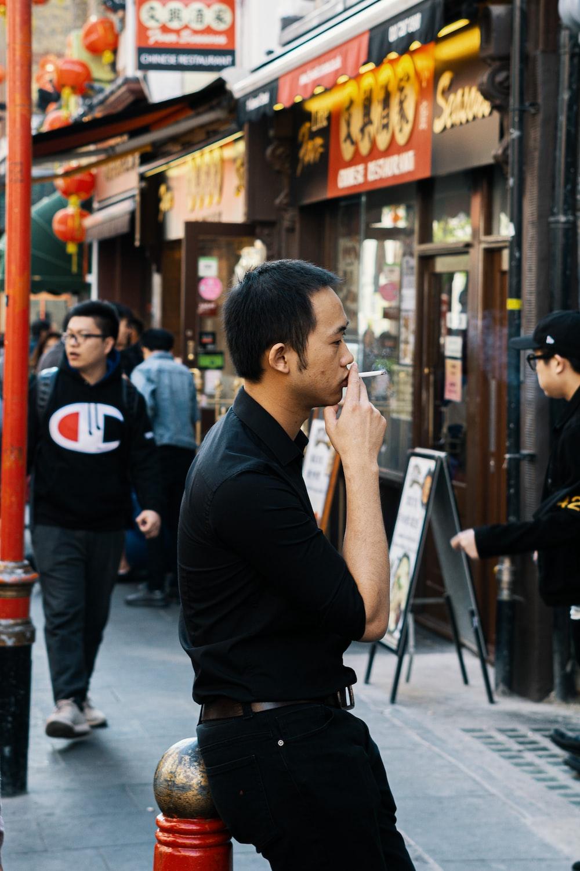 man in black long sleeve shirt holding smartphone