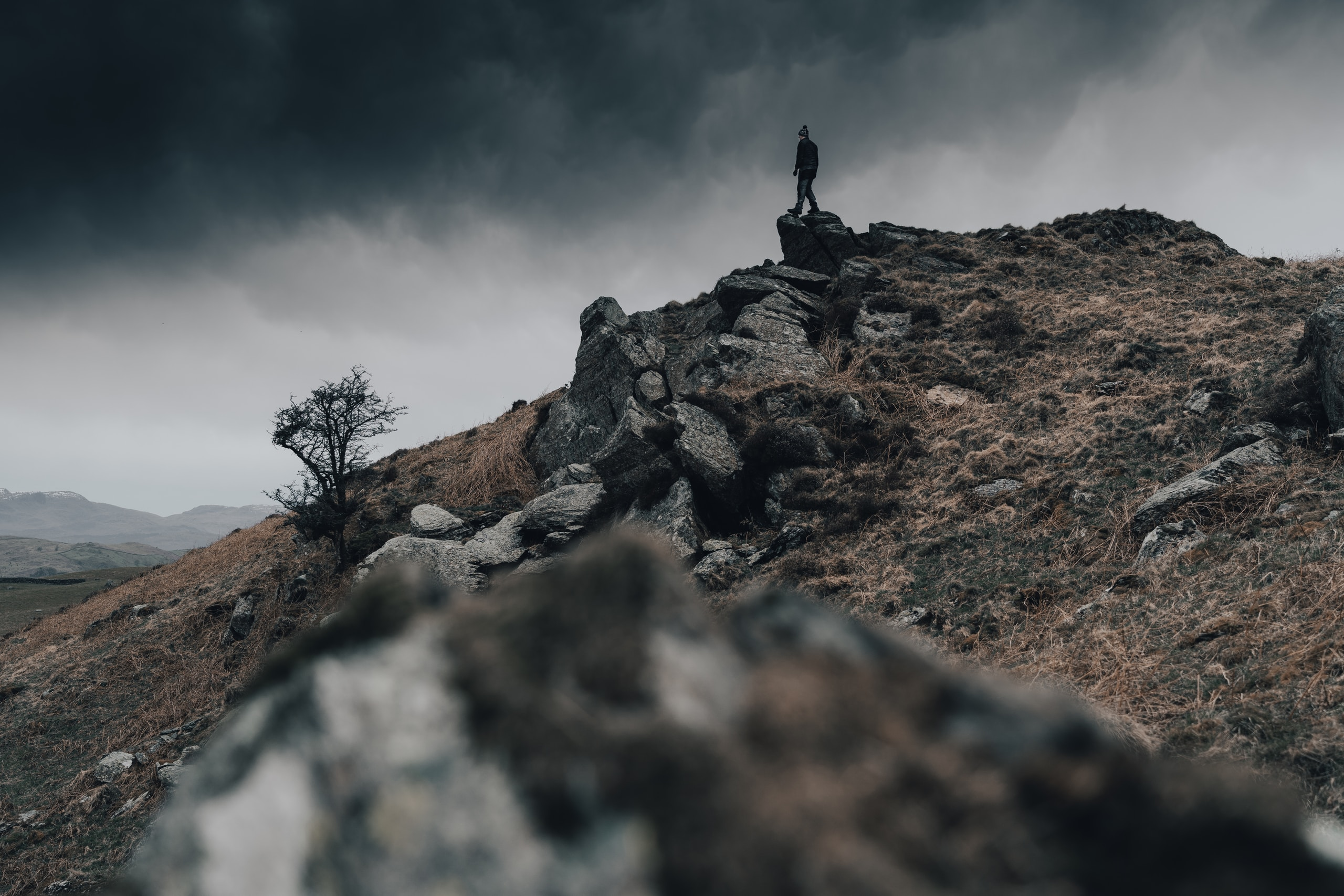 person sitting on rock under cloudy sky during daytime