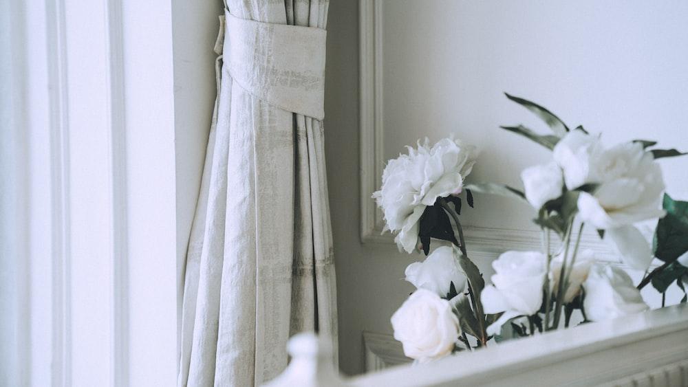 white roses on white wooden table